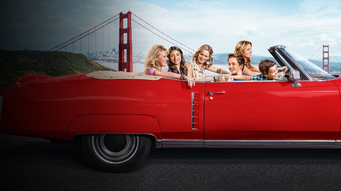 The cast of Fuller House on a convertible driving in front of the Golden Gate Bridge.