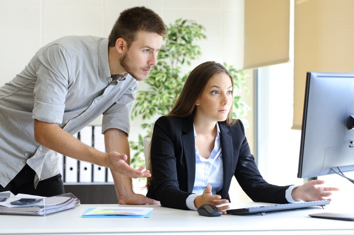 Two young business people, looking confused over a shared computer.