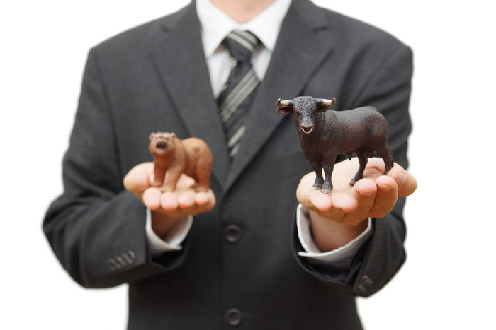 Man holding bull and bear with bull in focus