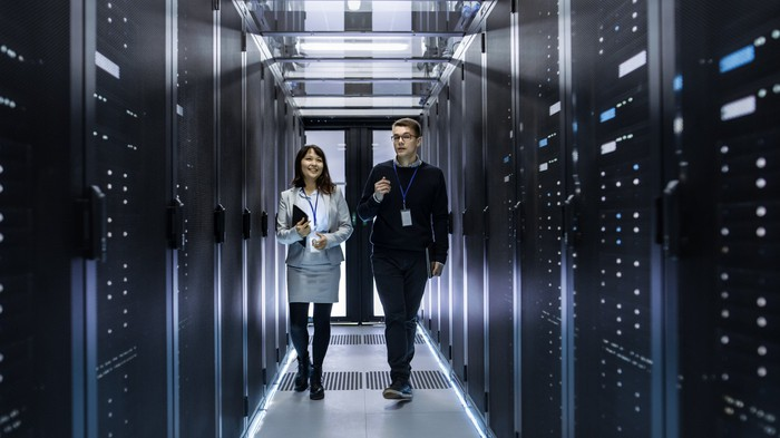 IT technicians walking through corridor of a data center with rows of rack servers.