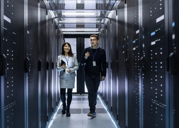 IT technicians walking through corridor of data center with rows of rack servers