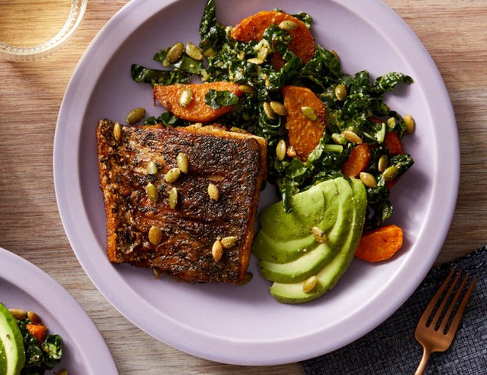 Mexican-spiced barramundi (fish) with kale, sweet potato, and avocado salad on white plate.