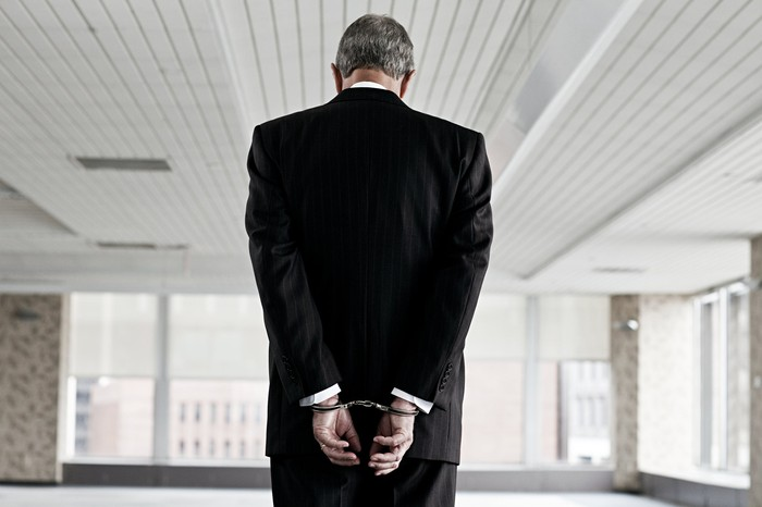 A person in a suit handcuffed behind their back.