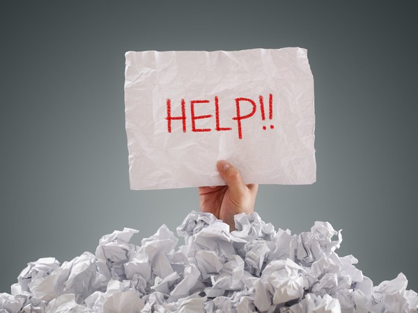 person buried under paper holding help sign debt