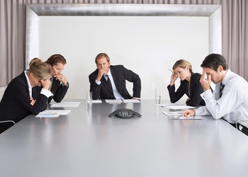 Management team around conference table looking worried