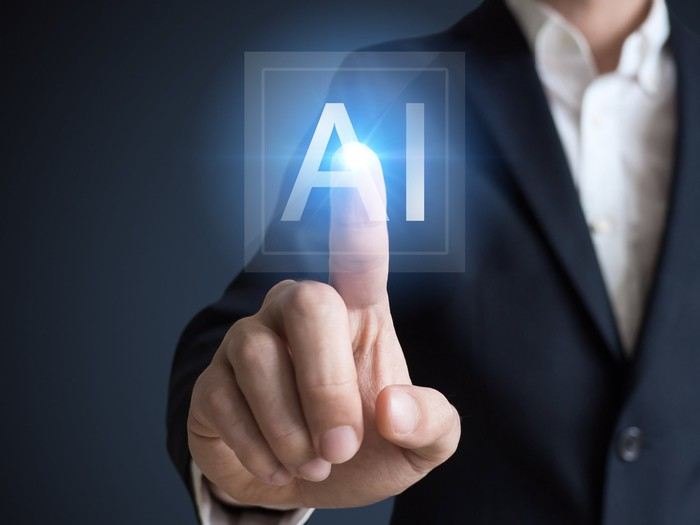 A man in professional clothes points to an AI icon on a transparent touchscreen.