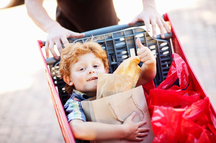 A small boy being pushed in a shopping cart clutches a bag while giving a thumbs-up sign.