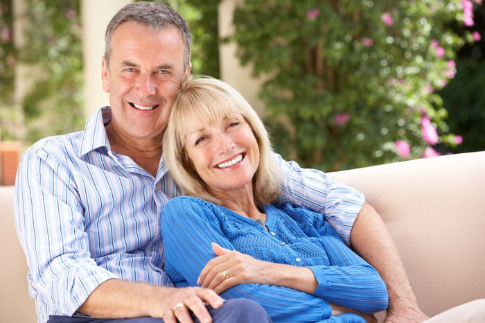 Smiling older couple sitting on a couch