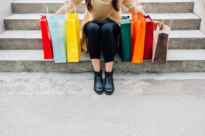 A woman sitting down on steps with colorful shopping bags on both sides of her.