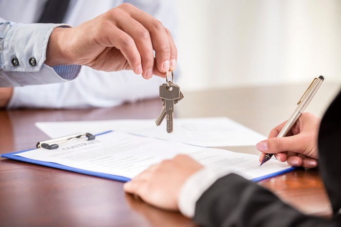 Handing keys to person signing paperwork.