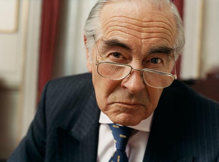 A scowling elderly wealthy man wearing a suit.