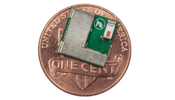 Small semiconductor chip sitting on top of a penny