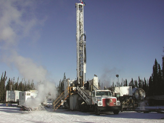 Drilling rig with associated buildings in a winter setting with snow on the ground and pine trees surrounding the area.