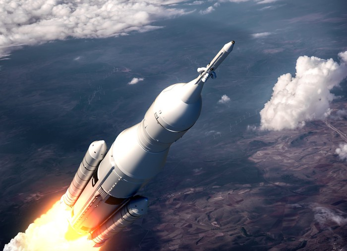 A rocket soars through the clouds headed toward space.