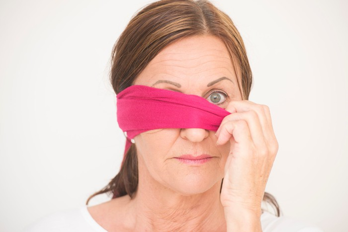 mature woman peaks out one eye from behind a purple blindfold.