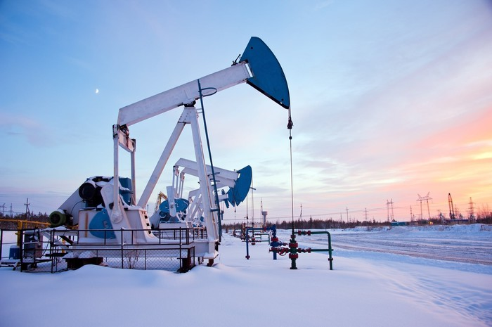 Giant pumpjack standing in snow at sunset.