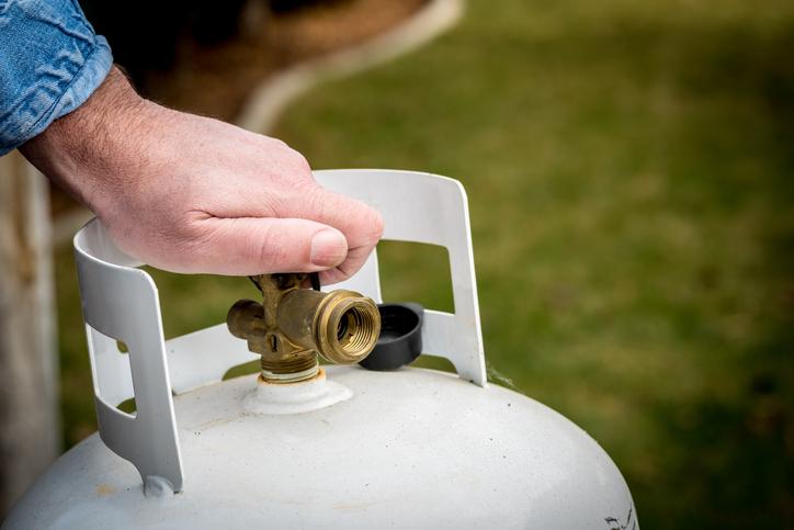 A man turns a knob on a propane tank.