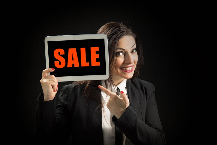 Word sale on tablet with woman holding it