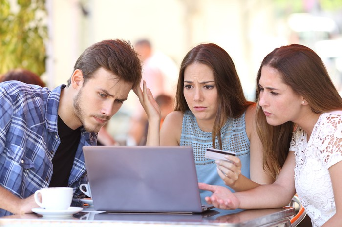 Three friends looking at a computer screen perplexed, as one holds a credit card.