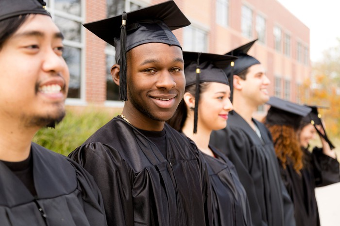 Row of college graduates in black gowns smiling on a hazy day in front of a building.