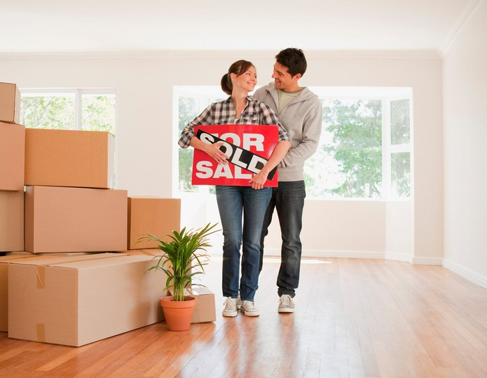 Younger couple holding sold sign, standing next to moving boxes.