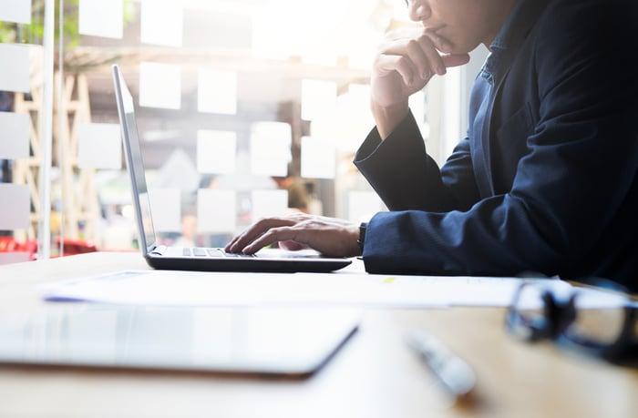 Man sitting at desk looking at computer.