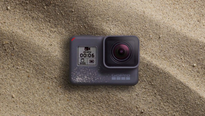 The Hero 6 Black camera resting on sand.