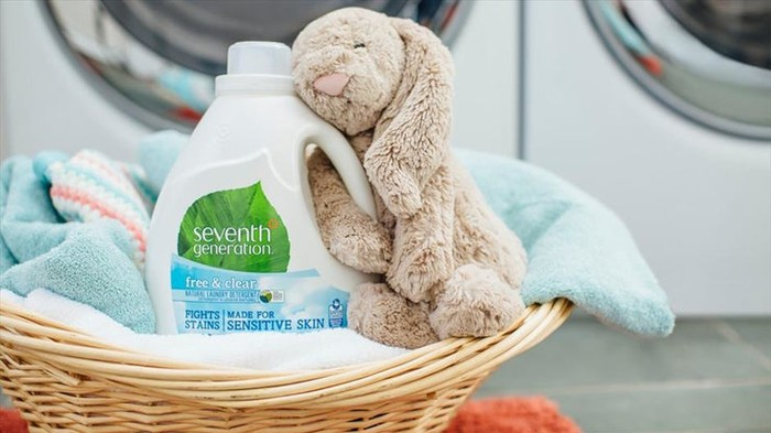 "Plush dog toy with arm wrapped around a bottle of Unilever's ""Seventh Generation"" brand laundry detergent in laundromat."