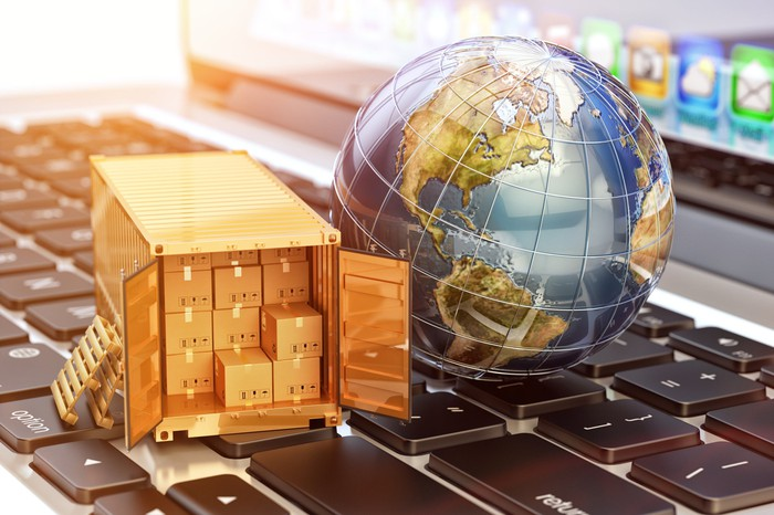 A miniature globe and a truck filled with packages on top of a keyboard.