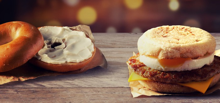 A sausage egg McMuffin and a bagel with cream cheese on it.