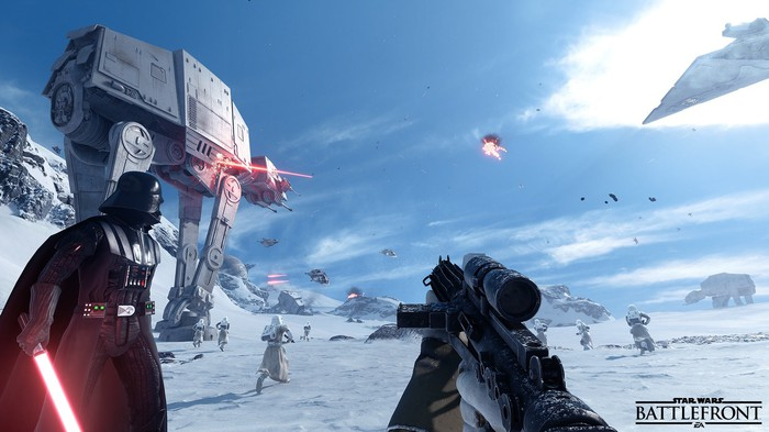 A character holding a gun from the first-person perspective looking at Darth Vader and an AT-AT walker in EA's game Star Wars Battlefront II.