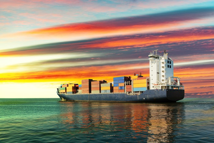 A sailing container ship at sunset on the sea.