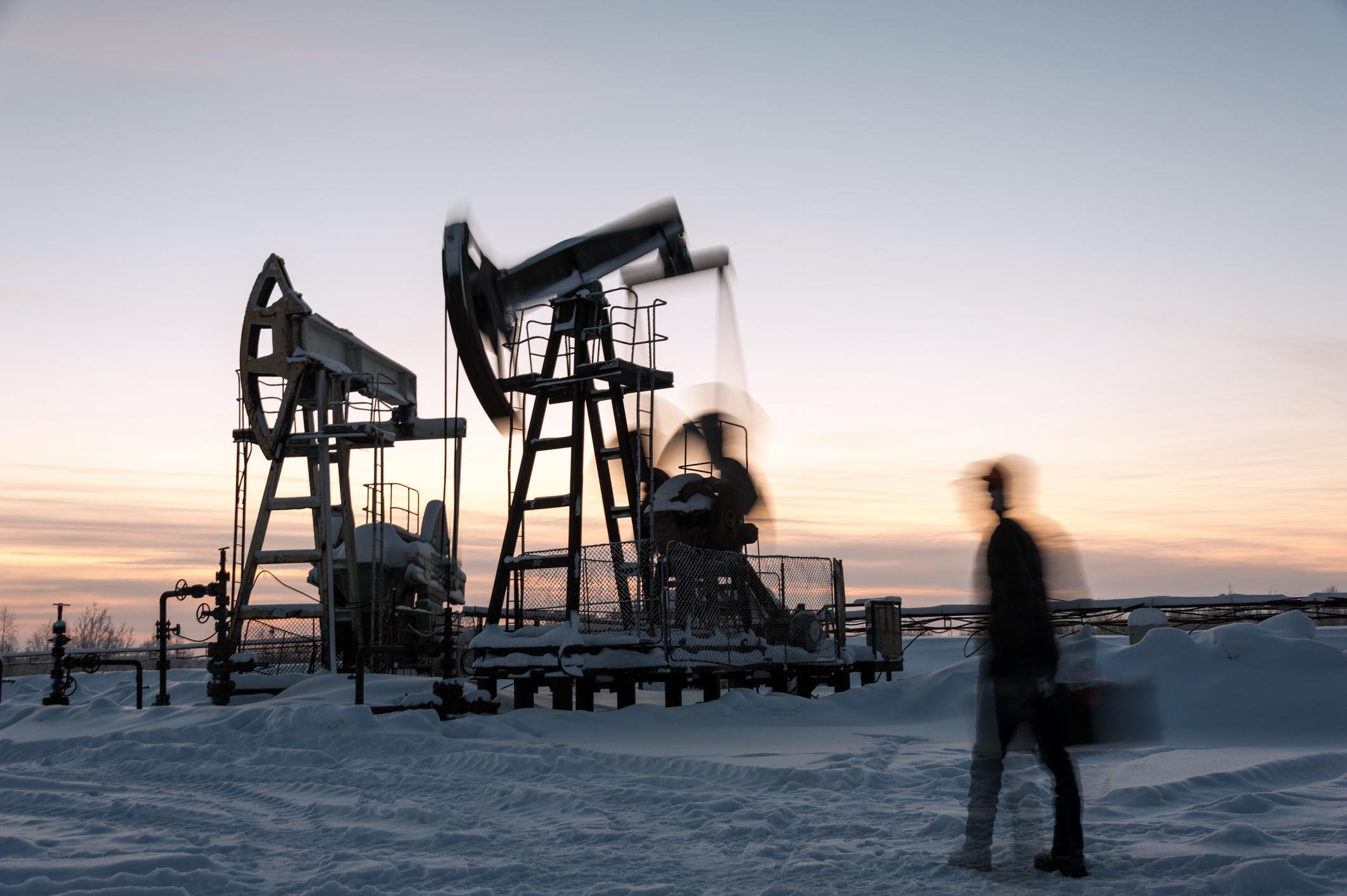 Oil worker walking toward a pumpjack in wintertime.