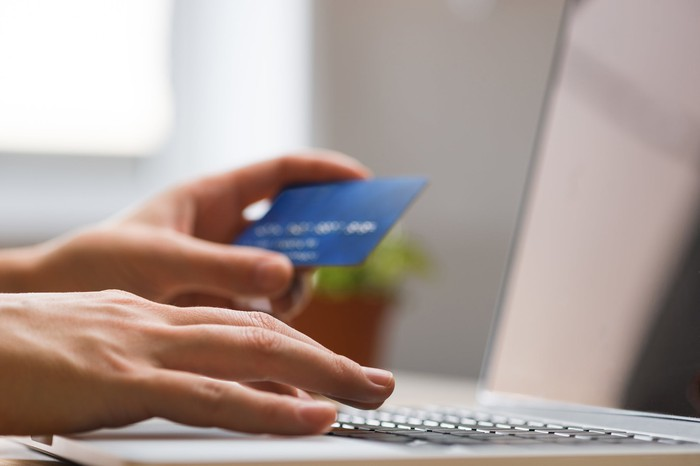 One hand holding a credit card while the second types on a laptop keyboard.