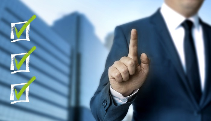A man in a suit holds an index finger up next to three checkboxes.