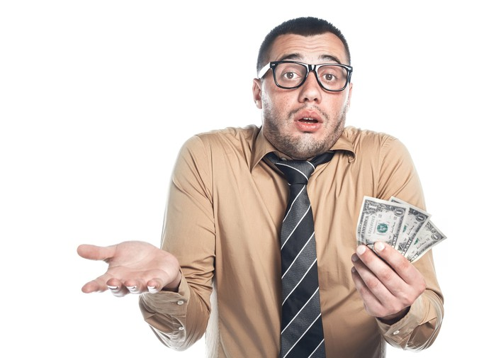 Man shrugging while holding some dollar bills