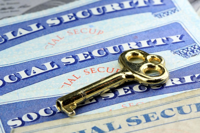 Social Security cards laid out flat on a surface, with a brass key on top.