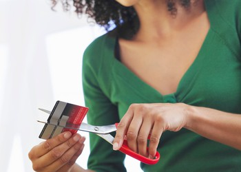 young woman cutting credit card in half with scissors debt POC