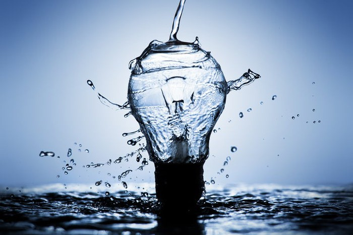 A light bulb made of water bursting over a pool of water.