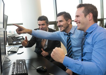 Happy Business Team Trading Stocks Getty