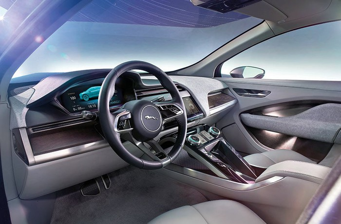 The interior of an I-PACE from the driver's side. Jaguar's leaping cat emblem is displayed on the wheel, and the displays are all electronic.