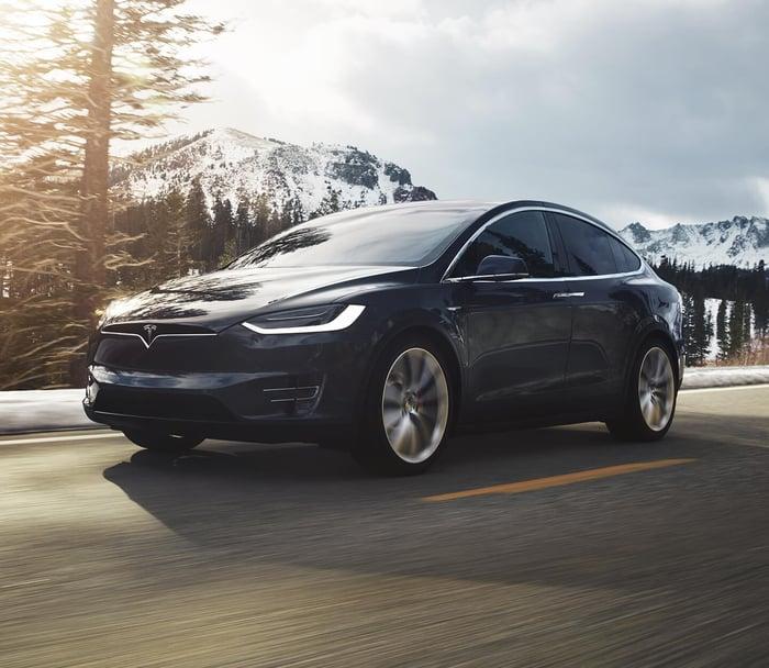 A black Tesla Model X driving on a mountain road.