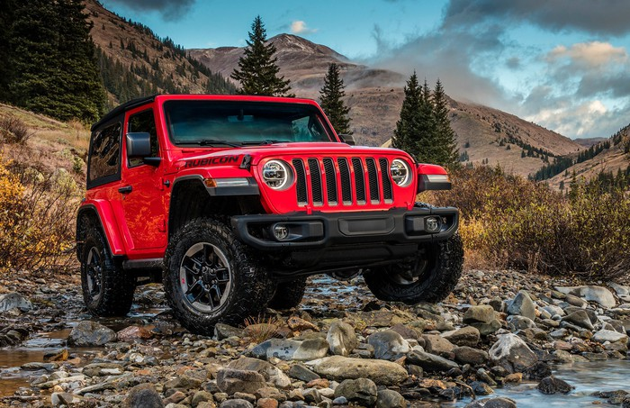 A red 2018 Jeep Wrangler SUV is parked next to a stream near a rough mountain trail.