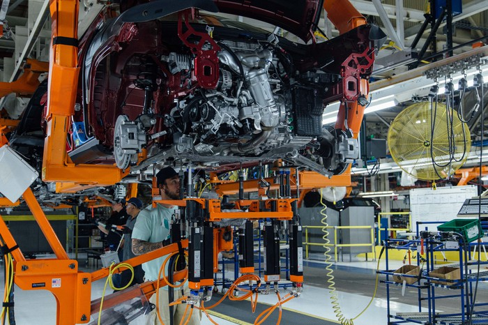 Workers attend to a partially-assembled Jeep Cherokee on the assembly line at FCA's Belvidere Assembly Plant in Belvidere, Illinois.