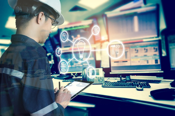 A man wearing a hard hat using a tablet in room of computer monitors. An overlay of industrial tool icons.