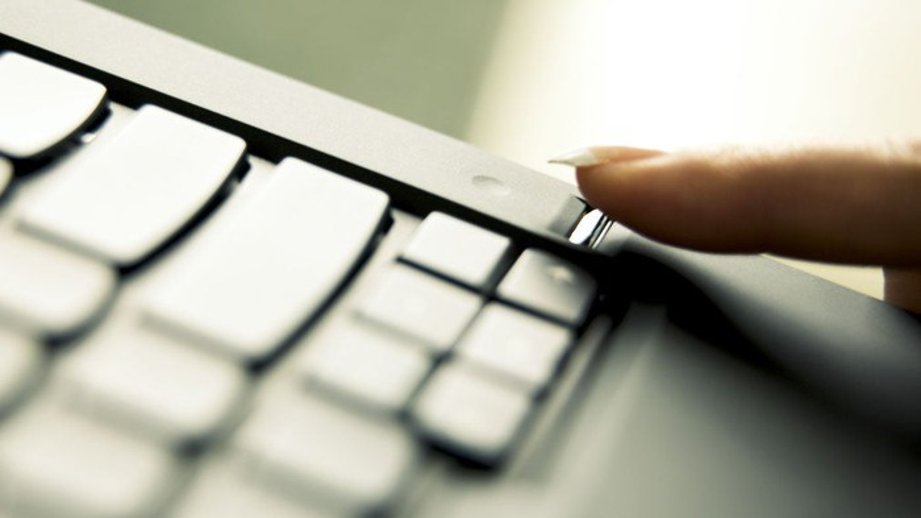 Woman using a fingerprint sensor on a laptop.