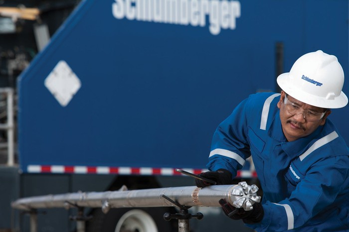 Oilfield worker working on pipe, wearing a Schlumberger white hard hat in front of a Schlumberger trailer.