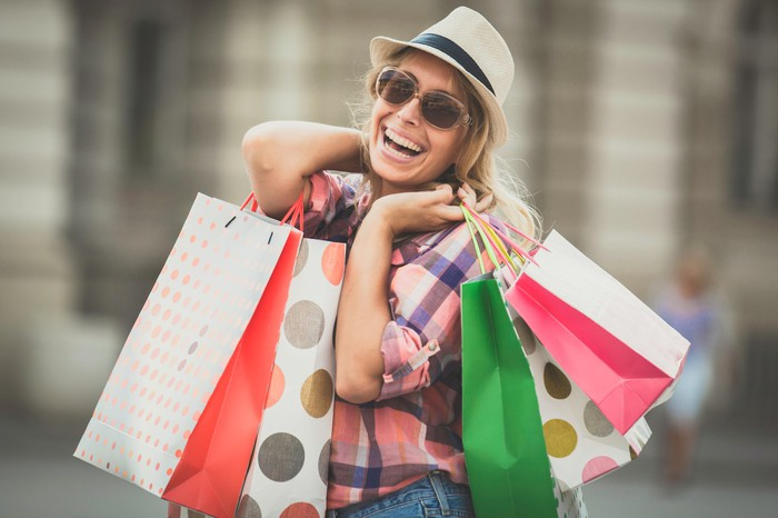 A smiling woman holds several shopping bags.