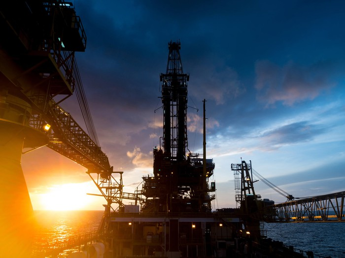 An offshore oil platform with the sun rising in the background.