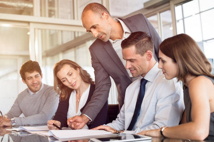 Professional male standing over a group of coworkers, reviewing documents